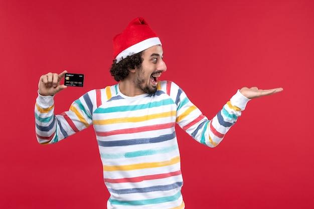 Vue de face jeune homme tenant une carte bancaire sur le mur rouge émotion mâle rouge vacances