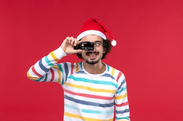 Vue de face jeune homme tenant une carte bancaire sur le mur rouge émotions de vacances mâles rouges
