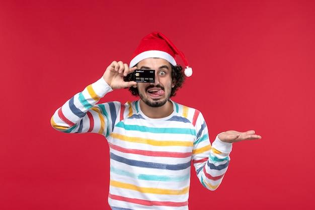 Vue de face jeune homme tenant une carte bancaire sur le mur rouge mâle rouge vacances émotion