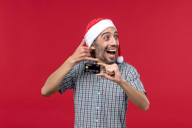 Vue de face jeune homme tenant une carte bancaire noire sur un bureau rouge