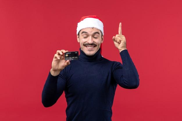 Vue de face jeune homme tenant une carte bancaire noire sur fond rouge