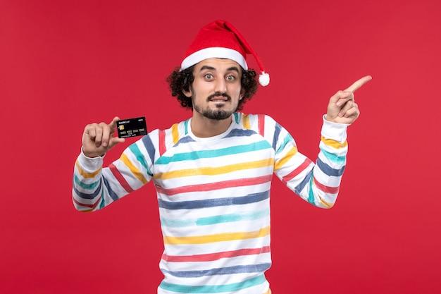 Vue de face jeune homme tenant une carte bancaire noire sur le mur rouge de l'argent de vacances du nouvel an rouge