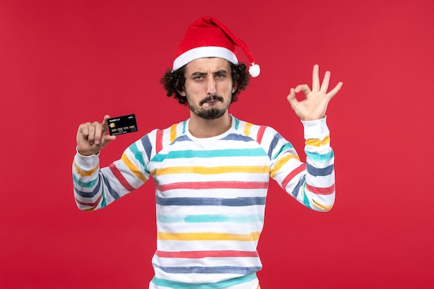 Vue de face jeune homme tenant une carte bancaire noire sur le mur rouge argent vacances du nouvel an rouge