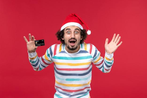 Vue de face jeune homme tenant une carte bancaire noire sur le mur rouge argent vacances d'émotions mâles rouges