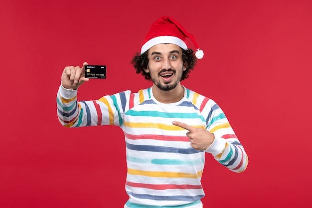 Vue de face jeune homme tenant une carte bancaire noire sur mur rouge nouvel an argent vacances rouge