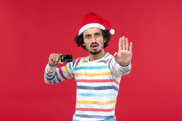 Vue de face jeune homme tenant une carte bancaire noire sur un mur rouge nouvel an argent vacances rouges