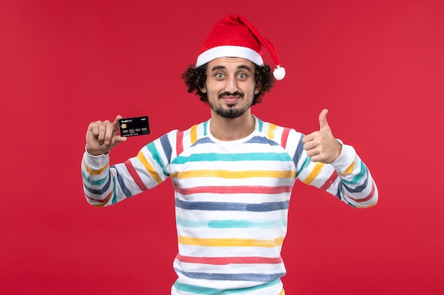 Vue de face jeune homme tenant une carte bancaire noire sur un mur rouge vacances de l'argent du nouvel an rouge