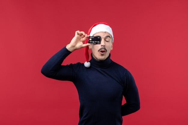 Vue de face jeune homme tenant une carte bancaire noire sur plancher rouge vacances nouvel an émotion