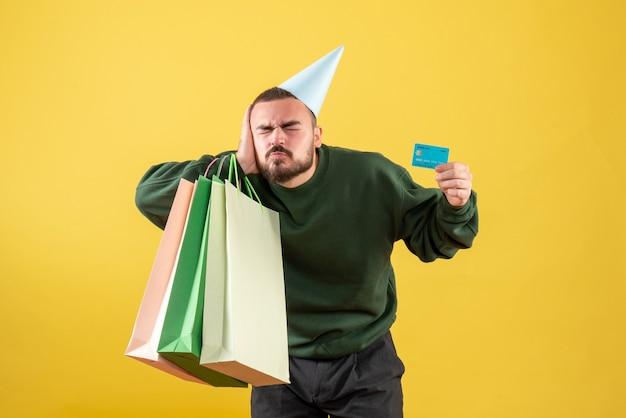 Vue de face jeune homme tenant une carte bancaire et des paquets d'achat sur fond jaune