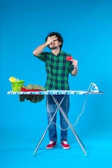 Vue de face jeune homme tenant une carte bancaire rouge sur fond bleu maison de blanchisserie argent laver les travaux ménagers faire du shopping