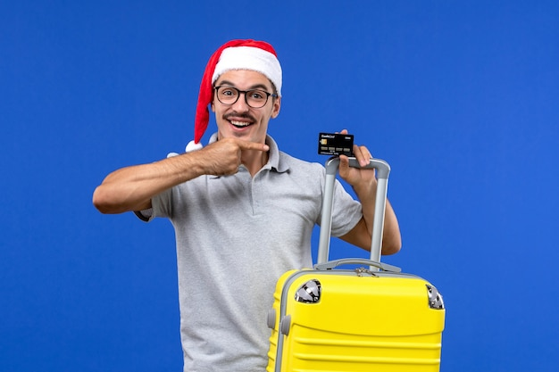 Vue de face jeune homme tenant une carte bancaire sac jaune sur une émotion de vacances voyage fond bleu