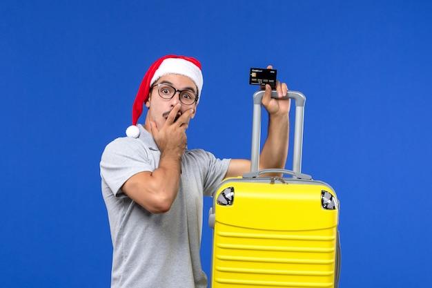 Vue de face jeune homme tenant une carte bancaire sac jaune sur le mur bleu voyage émotion vacances