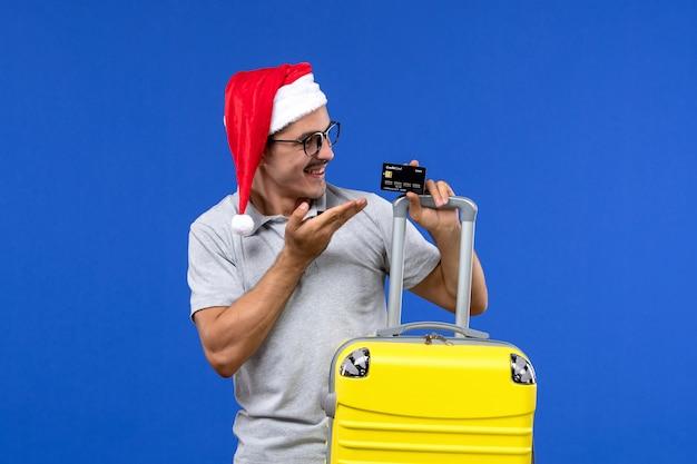 Vue de face jeune homme tenant une carte bancaire sac jaune sur mur bleu voyage vacances émotion