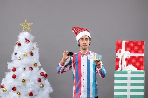 Vue de face jeune homme tenant une carte et un billet de voyage autour de l'arbre de noël et des cadeaux