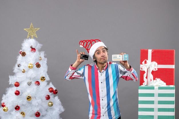 Vue de face jeune homme tenant une carte et un billet de voyage près de l'arbre de noël avec des jouets de noël colorés