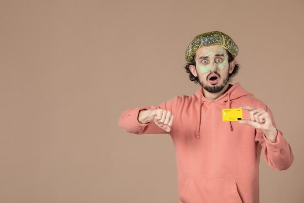Vue de face jeune homme tenant une carte de crédit sur fond marron spa soins du corps argent thérapie soins de la peau salon peau du visage