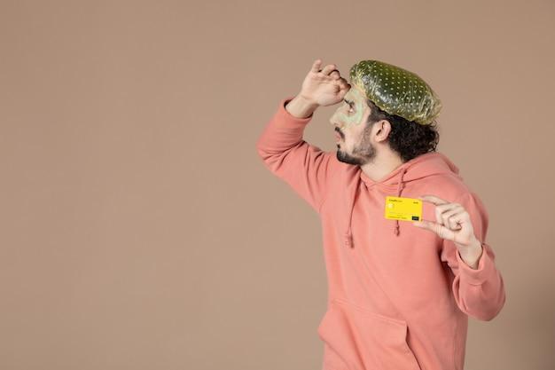 Vue de face jeune homme tenant une carte de crédit jaune sur fond marron couleur spa peau du visage soins du corps thérapie de l'argent salon de soins de la peau