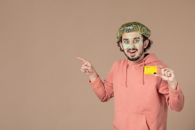 Vue de face jeune homme tenant une carte de crédit jaune sur fond marron peau salon soins de la peau soins du corps spa argent thérapie