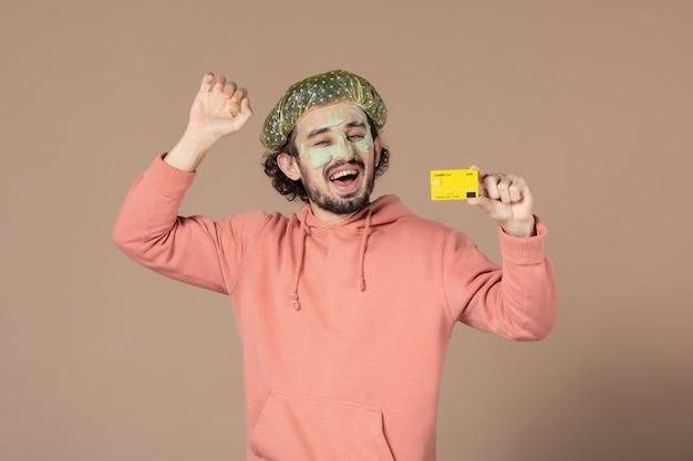 Vue de face jeune homme tenant une carte de crédit jaune sur fond marron peau salon thérapie soins de la peau soins du corps spa argent