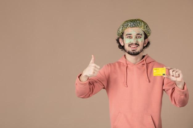 Vue de face jeune homme tenant une carte de crédit jaune sur fond marron peau spa soins du corps thérapie de l'argent soins de la peau du visage