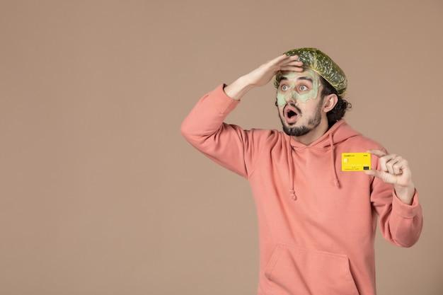 Vue de face jeune homme tenant une carte de crédit jaune sur fond marron peau de spa soins du visage du visage argent salon de soins de la peau