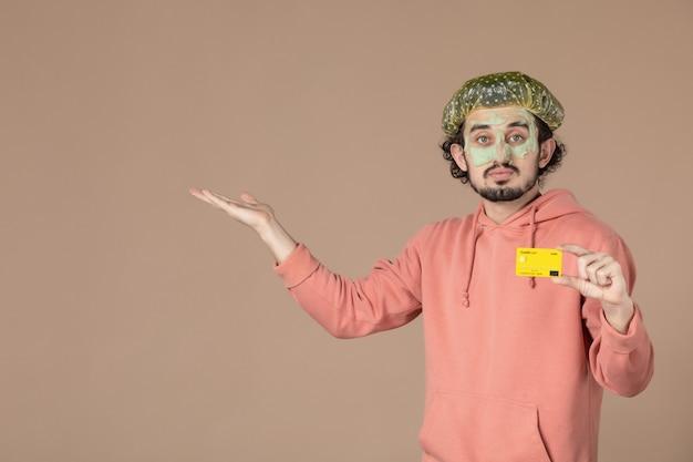 Vue de face jeune homme tenant une carte de crédit jaune sur fond marron peau de spa soins du visage du visage thérapie de l'argent couleur salon de soins