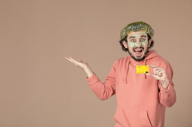 Vue de face jeune homme tenant une carte de crédit jaune sur fond marron peau de spa soins du visage du visage thérapie de l'argent salon de soins de la peau couleur