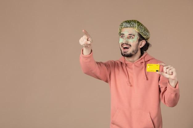 Vue de face jeune homme tenant une carte de crédit jaune sur fond marron peau de spa soins du visage du visage thérapie de l'argent salon de soins de la peau