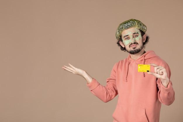 Vue de face jeune homme tenant une carte de crédit jaune sur fond marron peau de spa soins du visage du visage thérapie de l'argent soins de la peau
