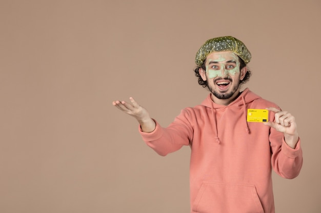 Vue de face jeune homme tenant une carte de crédit jaune sur fond marron peau de spa soins du visage thérapie salon de soins de la peau