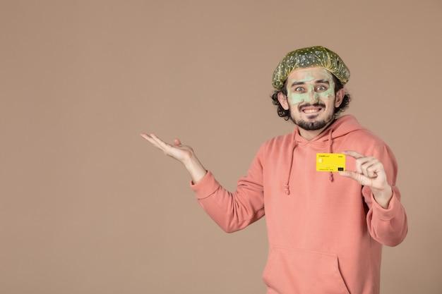 Vue de face jeune homme tenant une carte de crédit jaune sur fond marron peau spa thérapie de soins de la peau salon de soins du visage