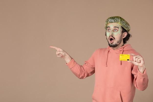 Vue de face jeune homme tenant une carte de crédit jaune sur fond marron salon de la peau soins du visage soins du corps spa argent thérapie couleur