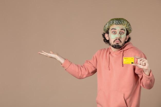 Vue de face jeune homme tenant une carte de crédit jaune sur fond marron salon de la peau soins du visage soins du corps spa argent thérapie couleurs