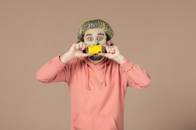 Vue de face jeune homme tenant une carte de crédit jaune sur fond marron salon de la peau soins du visage soins du corps spa argent thérapie