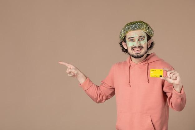 Vue de face jeune homme tenant une carte de crédit jaune sur fond marron salon de la peau soins du visage soins du corps spa argent