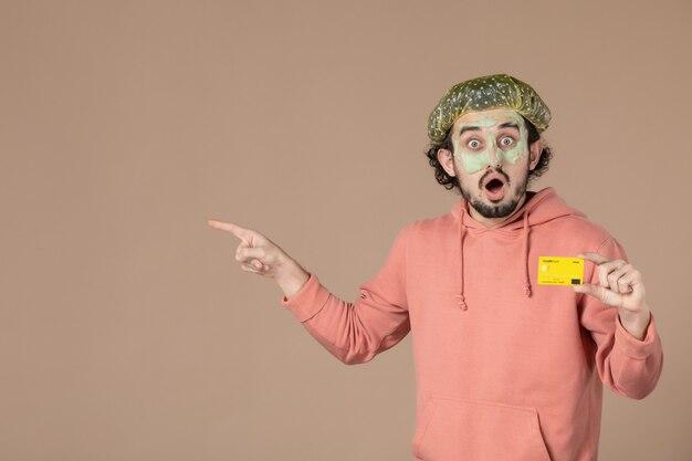 Vue de face jeune homme tenant une carte de crédit jaune sur fond marron salon de la peau soins du visage soins du corps thérapie spa