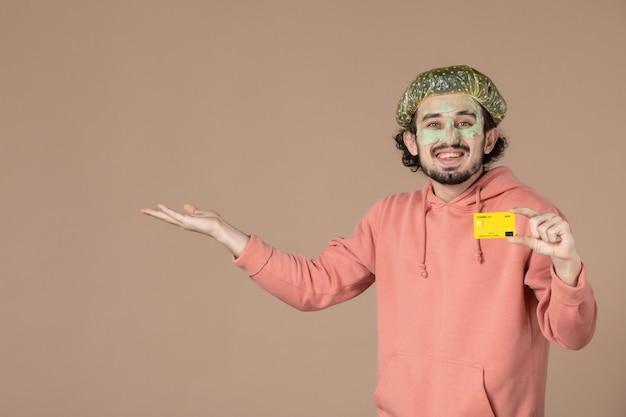 Vue de face jeune homme tenant une carte de crédit jaune sur fond marron salon de la peau soins du visage spa argent thérapie soins de la peau