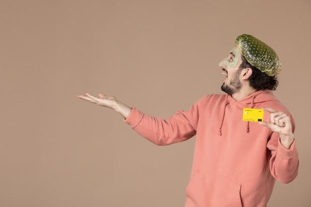 Vue de face jeune homme tenant une carte de crédit jaune sur fond marron salon de la peau soins de la peau soins du visage spa argent thérapie photo