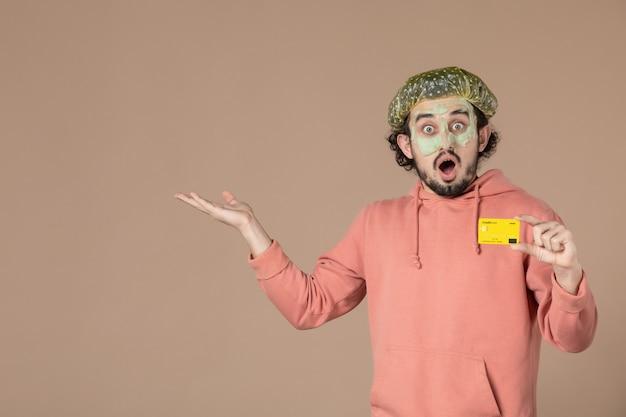Vue de face jeune homme tenant une carte de crédit jaune sur fond marron salon de la peau soins de la peau soins du visage thérapie de l'argent