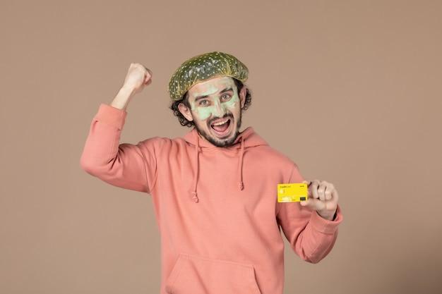 Vue de face jeune homme tenant une carte de crédit jaune sur fond marron salon de thérapie de l'argent soins de la peau peau du visage soins du corps spa