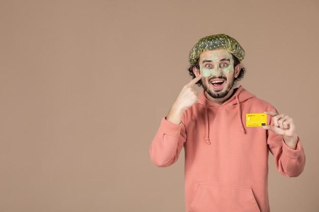 Vue de face jeune homme tenant une carte de crédit jaune sur fond marron spa argent thérapie salon de soins peau du visage