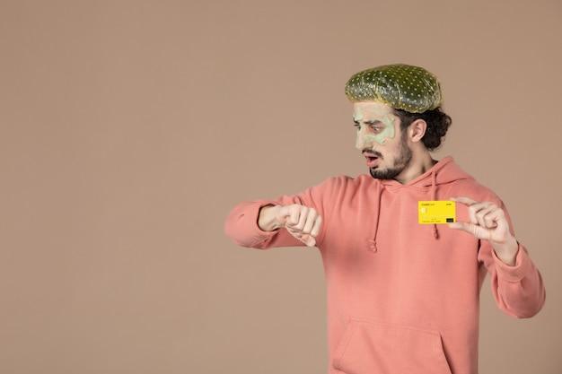Vue de face jeune homme tenant une carte de crédit jaune sur fond marron spa bodycare argent skincare salon peau du visage