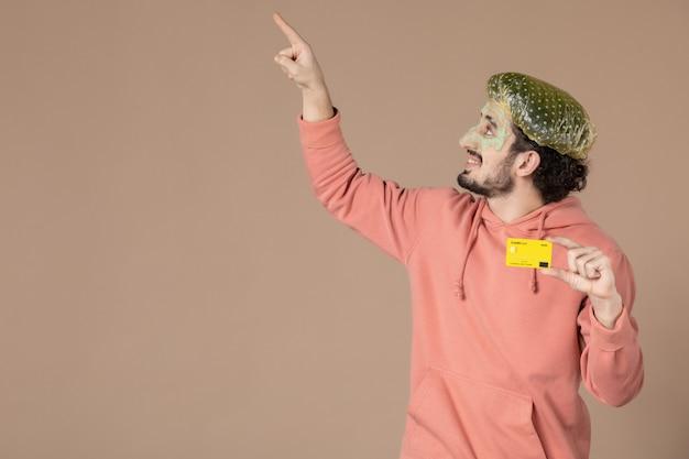 Vue de face jeune homme tenant une carte de crédit jaune sur fond marron spa couleur peau du visage soins du corps thérapie de l'argent salon de soins de la peau