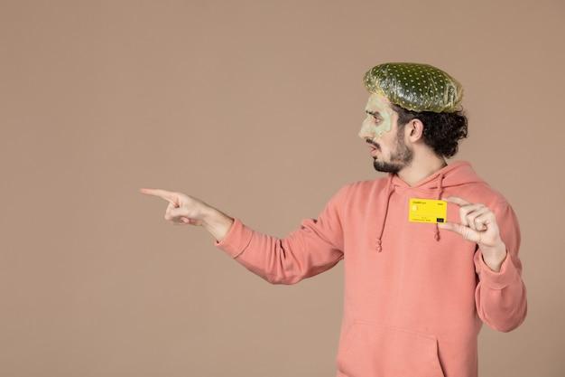 Vue de face jeune homme tenant une carte de crédit jaune sur fond marron spa couleur de la peau soins du visage du visage thérapie de l'argent salon de soins de la peau