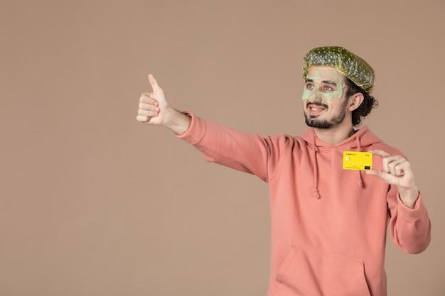 Vue de face jeune homme tenant une carte de crédit jaune sur fond marron spa peau du visage soins du corps argent thérapie salon