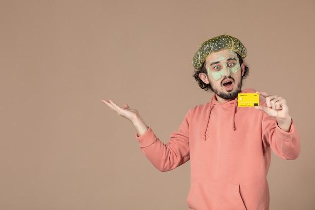 Vue de face jeune homme tenant une carte de crédit jaune sur fond marron spa peau soins du corps argent thérapie salon du visage