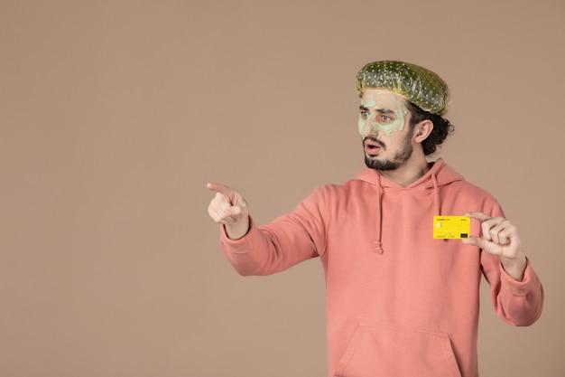 Vue de face jeune homme tenant une carte de crédit jaune sur fond marron spa peau soins du corps argent thérapie soins de la peau salon couleur du visage