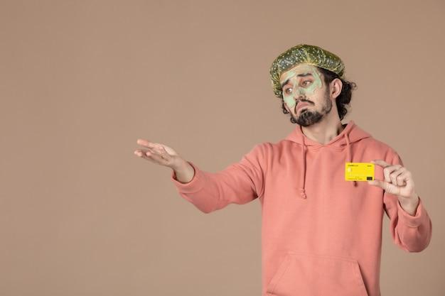 Vue de face jeune homme tenant une carte de crédit jaune sur fond marron spa peau soins du corps argent thérapie soins de la peau salon couleurs du visage
