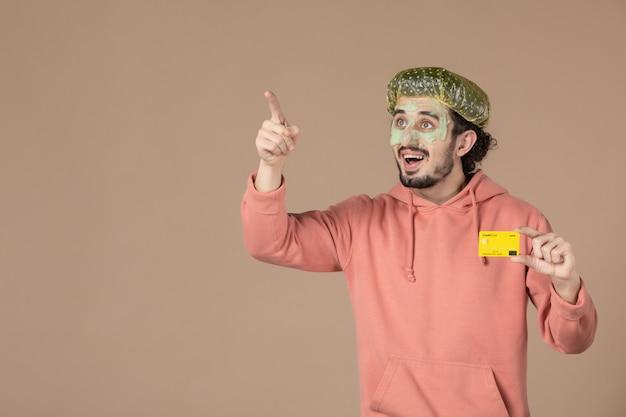 Vue de face jeune homme tenant une carte de crédit jaune sur fond marron spa soins du corps argent thérapie soins de la peau salon de la peau du visage