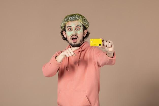 Vue de face jeune homme tenant une carte de crédit jaune sur fond marron thérapie de salon de la peau soins du visage soins du corps spa argent couleurs